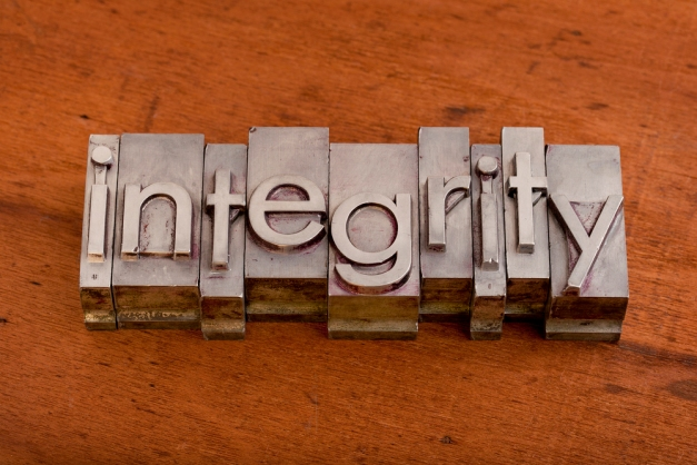 integrity word in vintage, metal letterpress printing blocks on scratched wooden background